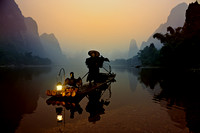 Fisherman at dawn on bamboo raft